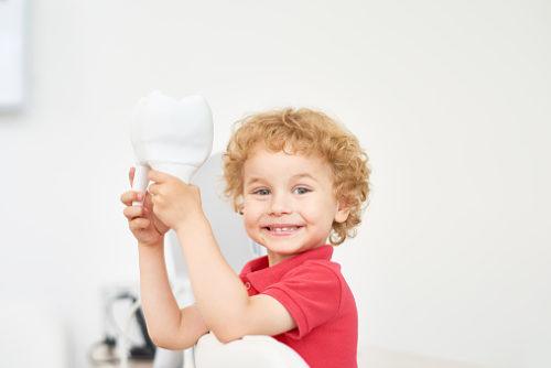 A child smiling after receiving dental care from Walker Dental Team